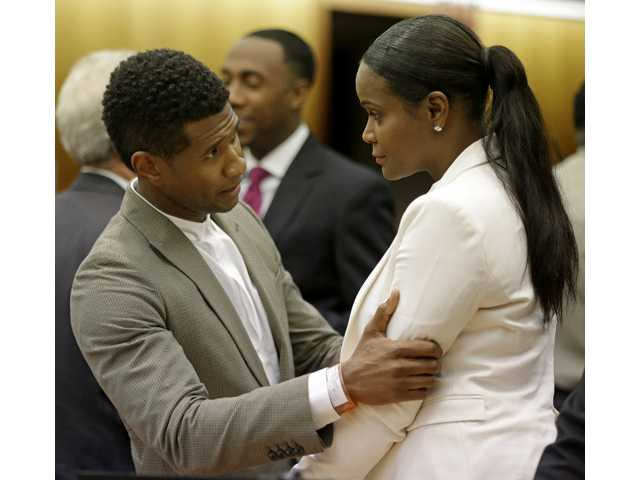 R&B singer Usher, left, embraces ex-wife Tameka Foster Raymond, after a judge dismissed an emergency request by Raymond seeking temporary custody of their two children on Friday in Atlanta.