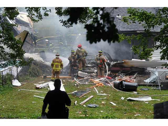 In this Friday, Aug. 9, 2013 photo, first responders work the scene of a small plane crash, in East Haven, Conn.