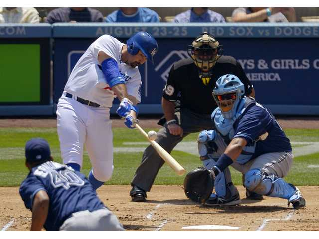 Los Angeles Dodgers' Adrian Gonzalez hits a two-run home run as Tampa Bay Rays starting pitcher Roberto Hernandez, front, and catcher Jose Molina and home plate umpire Paul Nauert watch Saturday in Los Angeles.