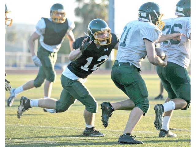 Cornerback Tyler Clark (12) closes in for a stop on running back Trevor Prata during Canyon's preseason football camp at Canyon High School on Friday.