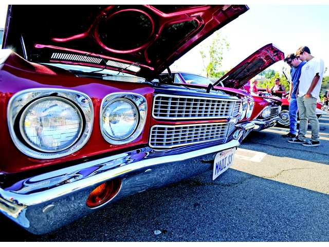Chip and David Reeves of Castaic check out some classic Chevrolet muscle cars at the Route 66 Classic Car show Saturday.
