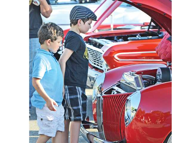 Angelo Mikalinis, 6, left, and brother Dominic, 9, examine the engine of a classic Ford hot rod on display at the Route 66 Classic Car show Saturday.