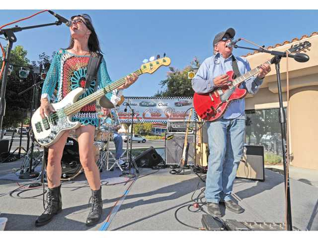 Jeanne Archer, left, on bass, and Scott Spindel, on lead guitar, perform classic rock on stage at the Route 66 Classic Car show.