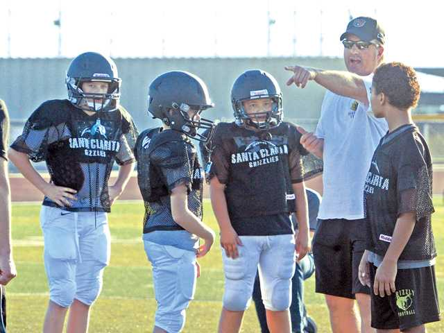 SCYSA Grizzlies offensive coordinator Ron Liljedahl works with the running backs during practice at Golden Valley High School on Friday.