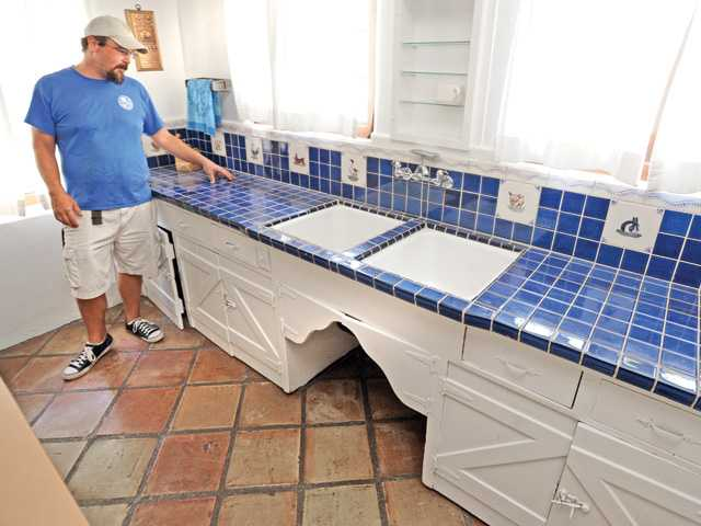 Recreation Services Supervisor Jared Didier describes the counter top tiles, cabinets  and handmade adobe floor tiles in the kitchen of the Adobe Ranch House at Tesoro Adobe Historic Park on Friday. Photo by Dan Watson.