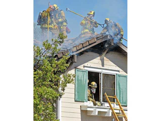 Firefighters ventilate the smoldering roof of a two-story house in the 27700 block of Essex Place in Valencia on Monday. Signal photo by Jonathan Pobre