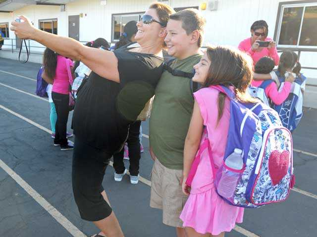 From left, Tammera Rice takes a photo with fifth-grader Sheldon, 10, and second-grader Michaela, 7, on the first day of school at Peachland. Signal photo by Jonathan Pobre