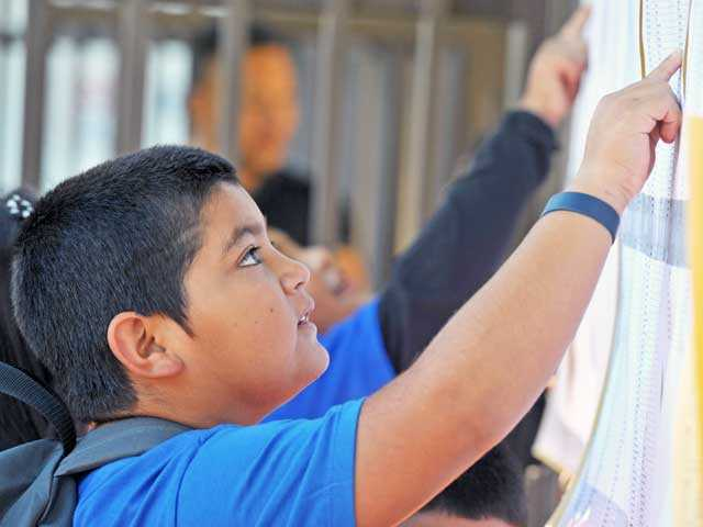 Sixth-grader Rigoberto Barron, 11, checks for his room assignment as students return to school at Peachland Elementary on Tuesday. Signal photo by Jonathan Pobre