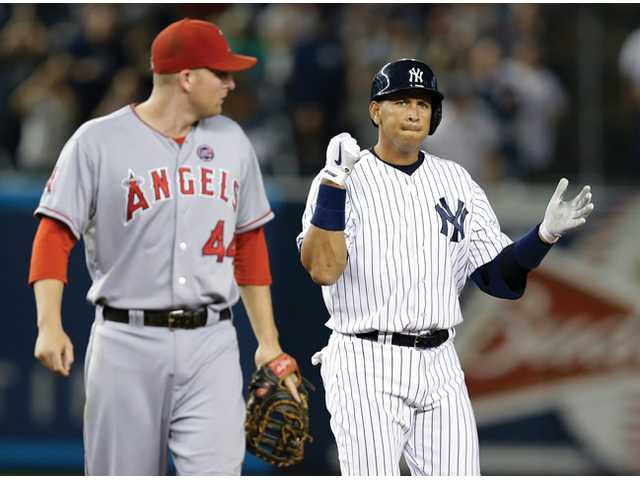 Los Angeles Angels first baseman Mark Trumbo (44) looks over his shoulder as New York Yankee Alex Rodriguez reacts after hitting a sixth-inning, two-run double Tuesday in New York.