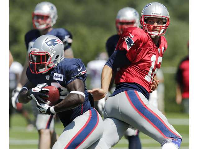 New England Patriots quarterback Tom Brady, right, hands off to running back Leon Washington during a practice in Foxborough, Mass. on Wednesday.