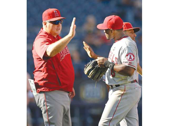 Los Angeles Angels manager Mike Scioscia, left, greets third baseman Chris Nelson after the Angels' victory over the New York Yankees on Thursday in New York.