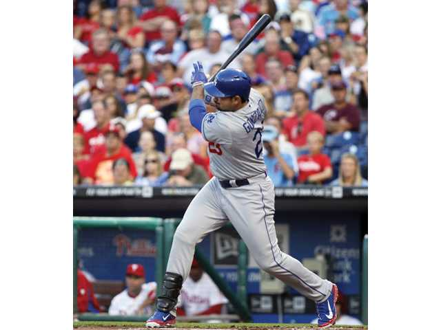 Los Angeles Dodgers' Adrian Gonzalez follows through on a grounder that scored Carl Crawford  against the Philadelphia Phillies on Saturday in Philadelphia.