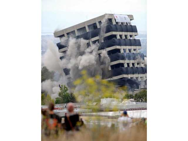 Warren Hall is imploded on the campus of Cal State East Bay in Hayward, Calif., on Saturday, Aug. 17, 2013. The former administration building has been vacant for two years after it was declared seismically unsafe.
