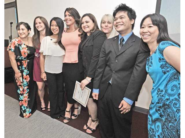 Eight members of the graduating class of the Medical Laboratory Technician Program pose for family photos after receiving their pins and certificates at the completion ceremony held at College of the Canyons University Center on Thursday evening. From left, Antonieta Casas, Ashley Horst, Rachel Arugay, Sarah Schroyer, Charlotte Ruiz, Cindy MacLennan, George Manzano, and Zheling Feng.