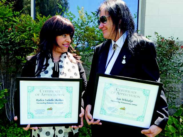 """Rodica Isabella Shaldan and Ron Whitaker hold their certificates of appreciation for """"Outstanding Humanitarian Service"""" from the Santa Clarita Valley Food Pantry."""