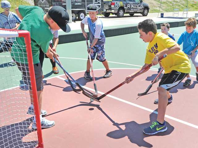 Goalie Ethan LeBlanc, 11, left, tries to block the shot by Jared Rahmiani, 11, right, during a hockey match on the L.A. Kings rubber-ball hockey rink at the fifth annual Youth Sports and Healthy Family Festival held at the Santa Clarita Sports Complex in Santa Clarita on Saturday.