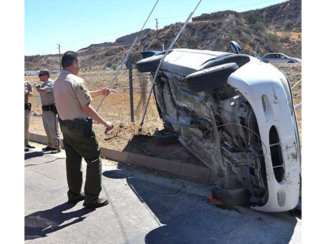A CHP officer stands near an overturned car off Interstate 5 near Parker Road in Castaic on Saturday. Photo by Rick McClure/For The Signal.