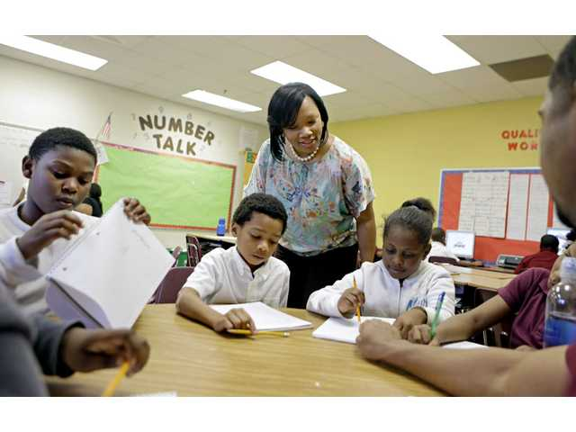 In this April 18, 2013 photo, Burgess-Peterson Elementary School principal Robin Robbins, center, meets with students during an after-school study program in Atlanta, in preparation for state standardized testing, soon to begin.