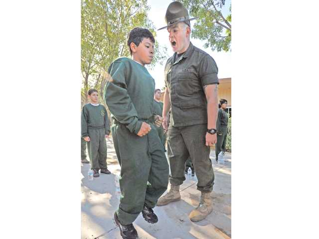 Drill instructor Matthew Webb reprimands VIDA academy participant Andrew Babaeghian, 12, left, as he runs in place during the morning inspection held at Bouquet Canyon Elementary School on Saturday. Photo by Dan Watson.