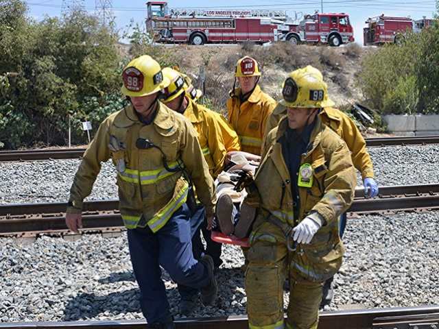 Los Angeles firefighters carry an injured victim from the scene after a car rolled off the southbound Interstate 5 just south of the truck lanes Monday. Rick McClure/for The Signal