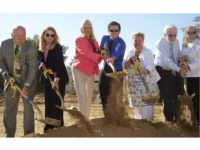 (From left to right) Steve Zimmer, Michele Jenkins, Dianne Van Hook, Ryan Joslin, Joan MacGregor, Bruce Fortine, and Cindy Schwanke throw dirt in the air during the groundbreaking of the new Culinary building in College of the Canyons on Monday. Photo by Steve Palma for The Signal.
