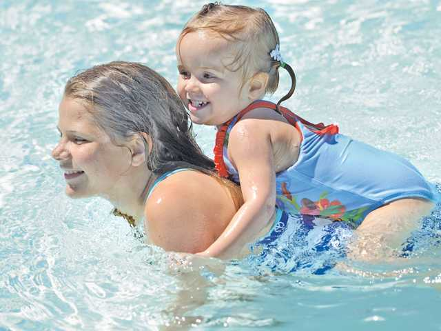 Sierra Meadows, 12, of Castaic gives a ride to Violet Casebolt, 2, as they cool off at the Castaic Sports Complex Aquatic Center on Tuesday. Signal photo by Dan Watson