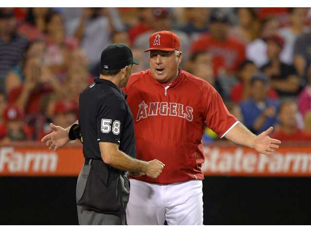 Los Angeles Angels manager Mike Scioscia, right, argues with home plate umpire Dan Iassogna on Monday in Anaheim.
