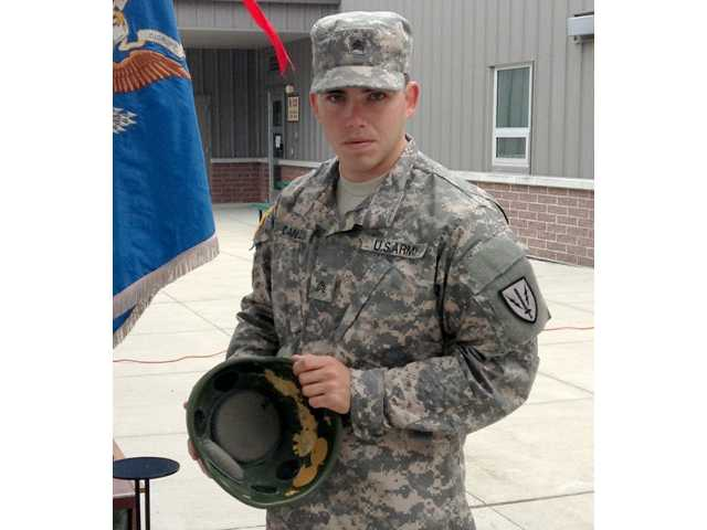 Sgt. Roger Daniels holds the helmet which saved his life in Afghanistan in 2012, on Joint Base Lewis-McChord, Wash. on Friday.