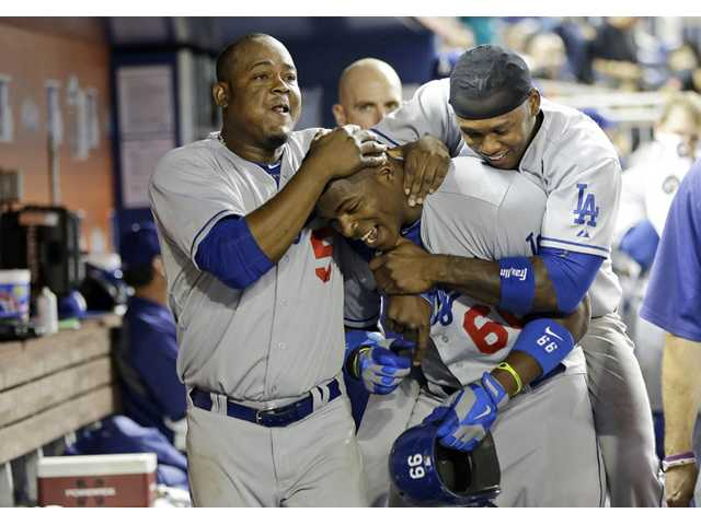 Los Angeles Dodger Yasiel Puig, center, is congratulated in the dugout by teammates Juan Uribe, left, and Hanley Ramirez, right, after hitting a home run in the eighth inning against the Miami Marlins on Tuesday.