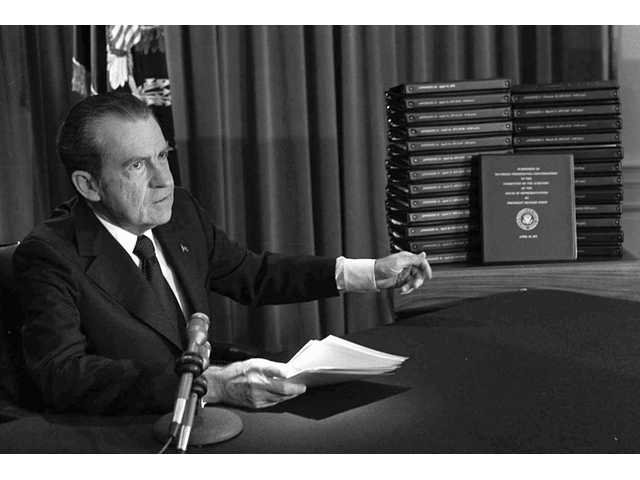 In this April 29, 1974, file photo, President Richard M. Nixon points to the transcripts of the White House tapes after he announced during a nationally televised speech that he would turn over the transcripts to House impeachment investigators in Washington.