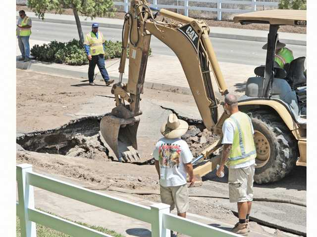 Crews work on the site of a water main break on Dickason Drive near Valencia High School on Thursday. Signal photo by Dan Watson