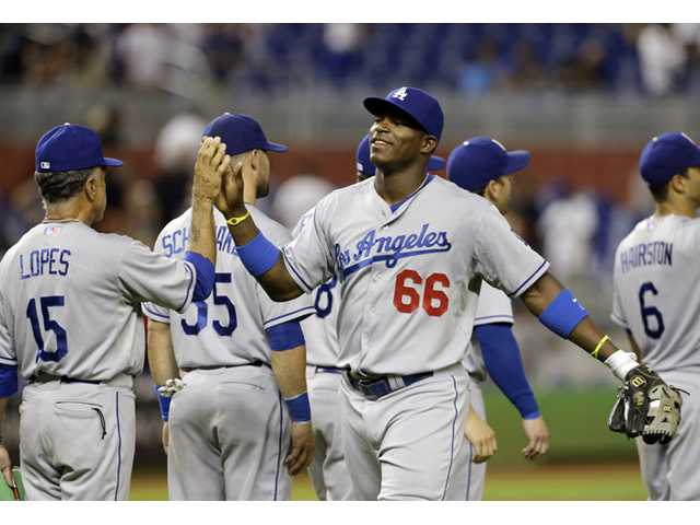 Los Angeles Dodgers right fielder Yasiel Puig (66) high-fives first base coach Davey Lopes (15) after the Dodgers defeated the Miami Marlins 4-1 Wednesday in Miami.