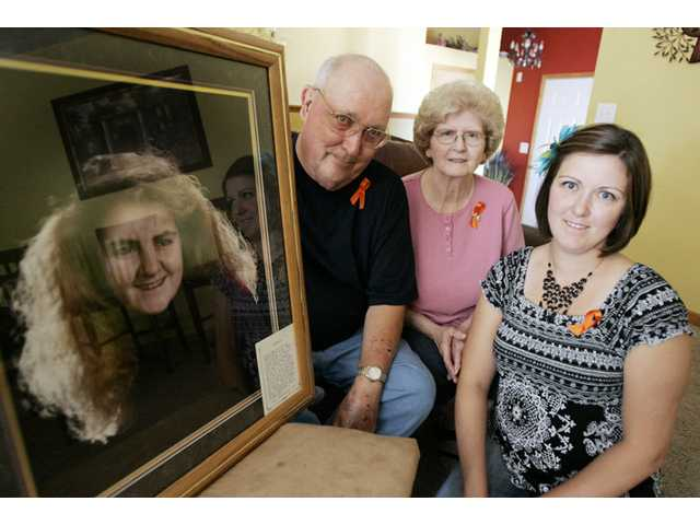 Ben and Karen Rison, along with their daughter, Wendy Hakes, pose with a photo of their late daughter and sister Rayna in LaPorte, Ind.