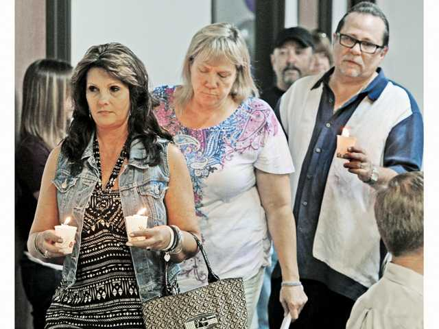 From left, mothers who lost sons to drugs,  Krissy McAfee and Kim Keener walk wtih Cary Quashen, founder of Action Family Foundation as they carry candles in remembrance of lives lost to drug overdose at the Action Foundation Candlelight Vigil, Drug Overdose Awareness & Memorial held at the Action Family Zone in Canyon Country on Friday.