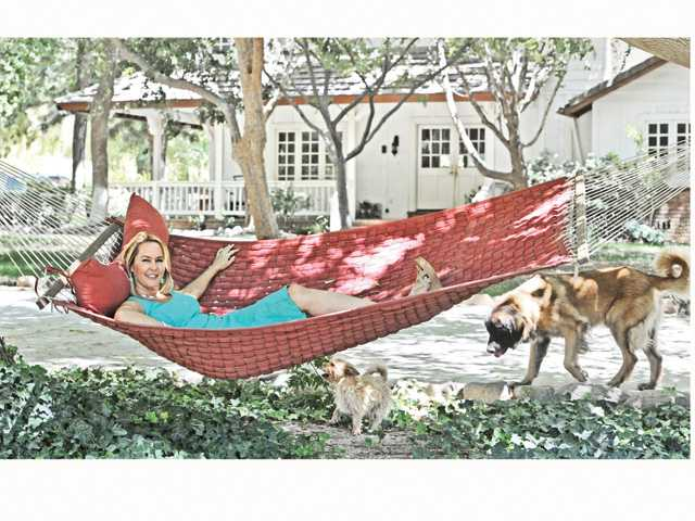 Erin Murphy enjoys her home Tranquil Veranda Ranch in Santa Clarita with dogs Shamrock, under her hammock, and Zuma, right.
