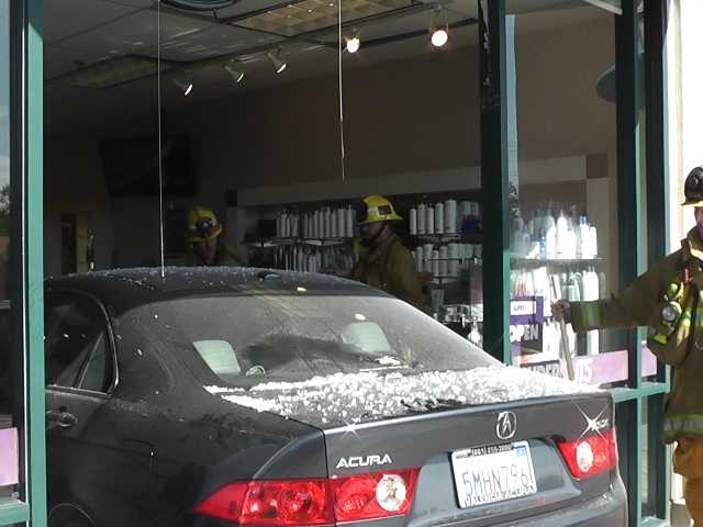 A compact car backs through the doors of a Supercuts in Valencia on Monday. The vehicle slammed about 30 feet into the salon about 9:15 a.m. Photo courtesy of Video Specialties