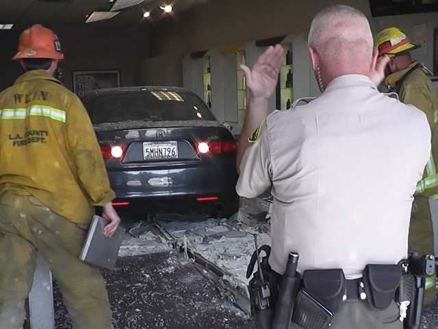A sheriff's deputy helps direct the driver of a car backing out of a Supercuts store Monday morning. The car crashed through the front windows of the salon in Valencia, injuring one person. Photo courtesy of Video Specialties