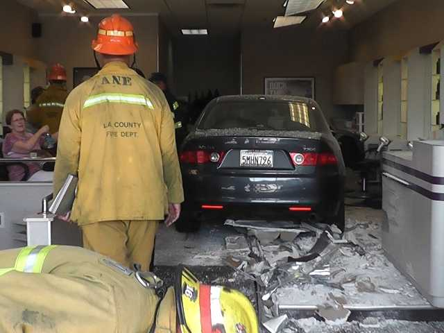 A car crashed through the front windows today of a Supercuts in Valencia, injuring one person.  Photo courtesy of Video Specialties