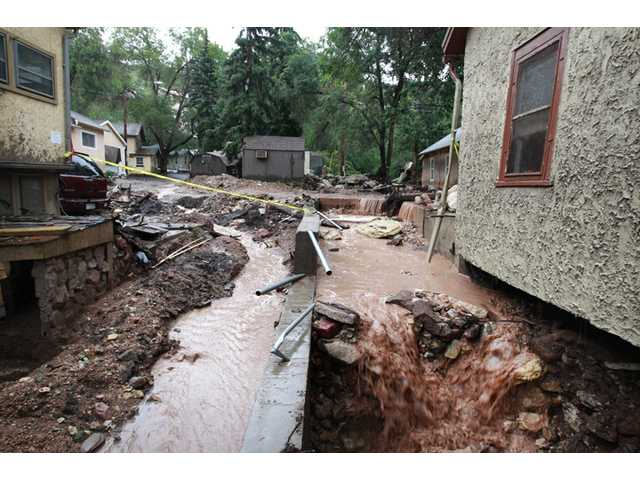Heavy rainstorm runoff spills through the foundations of debris-strewn homes destroyed in a flash flood, in Manitou Springs, Colo. on Aug. 13.
