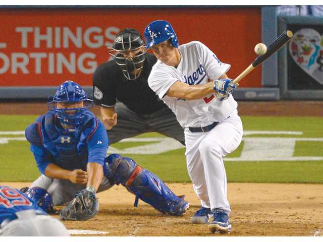 Los Angeles Dodger Zack Greinke, right, hits an RBI single as Chicago Cubs catcher Welington Castillo looks on during Monday night's game in Los Angeles.