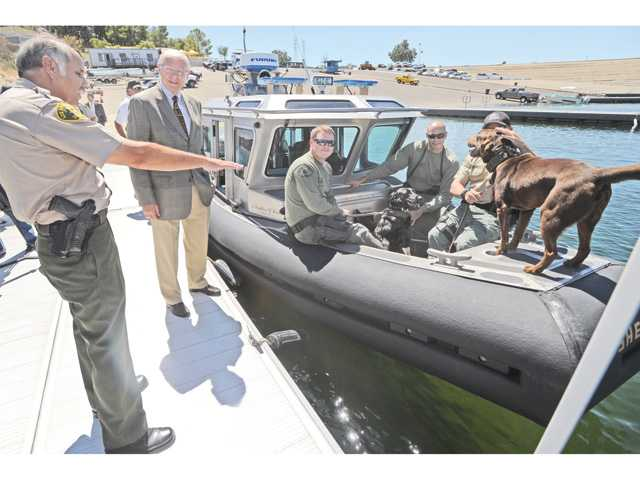Parks Bureau Captain Steve Smith, left, points out the features of the new Parks Bureau Fleet Safe Boat to L.A. County Supervisor Michael Antonovich, second left, at the dedication ceremony of the Sheriff's substation that will house L.A. County Marine Patrol Unit at Castaic Lake on Wednesday. L.A. County Sheriff's K9 unit dogs Ruby and Chip, right, stand on the bow of the boat. Photo by Dan Watson.
