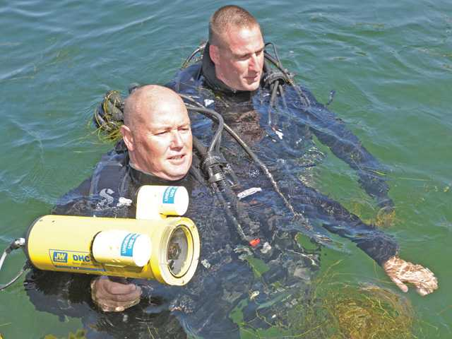 L.A. County Sheriff's Deputy divers, Kevin Nelson, left and Tim Cherry demonstrate the underwater hand camera as part of the equipment available at the new Parks Bureau substation. housing the L.A. County Marine Patrol Unit at Castaic Lake at the dedication ceremony on Wednesday morning. Photo by Dan Watson.