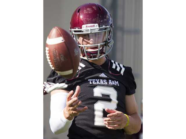 In this Aug. 5 photo, Texas A&M quarterback Johnny Manziel warms up during practice in College Station, Texas.