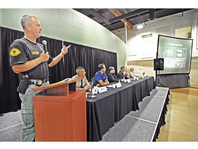 SCV Sheriff's Detective William Velek displays photos of drug paraphernalia on a screen for hundreds of attendees at the Heroin Kills Symposium held at the Santa Clarita Sports Complex on Wednesday evening. Photo by Dan Watson.