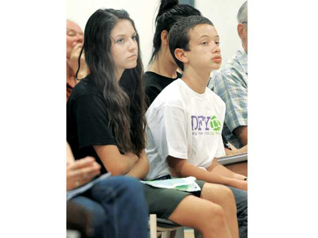 Drug Free Youth In Town Club members Bernadette Mercer, left, and Drayden Plush listen to speakers at the Heroin Kills Symposium held at the Santa Clarita Sports Complex on Wednesday evening. They later spoke to the hundreds of attendees at the event, advocating a drug free life at home and in school.  Photo by Dan Watson.