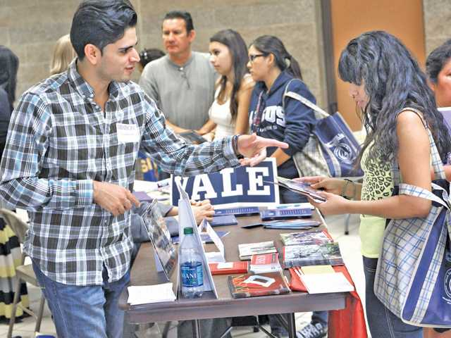 Denison University alumni representative Steve Flores, left, talks to student Kathy Martinez, 15, at the Hispanic College and Career Fair held at Golden Valley High School on Thursday. Over 35 colleges and local businesses set up tables for the second annual fair, according to an event coordinator. Photo by Dan Watson.