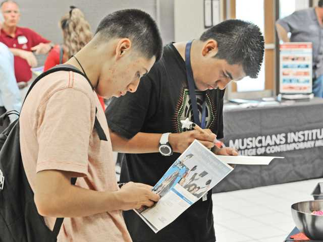 Golden Valley High Students Jesus Andrade, left, and Mauricio Mixco, 18, take material from Math Support Services at the Hispanic College and Career Fair at Golden Valley High School on Thursday. Photo by Dan Watson.