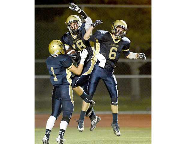 West Ranch wide receiver Gage Tynan (18) celebrates a touchdown catch with Brendan Moskal (1) and Joey Lau (6) against Hawthorne at Valencia High School.