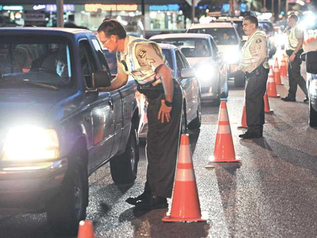 In this file photo Sheriff's deputies funnel cars into one lane at a DUI checkpoint on Lyons Avenue.