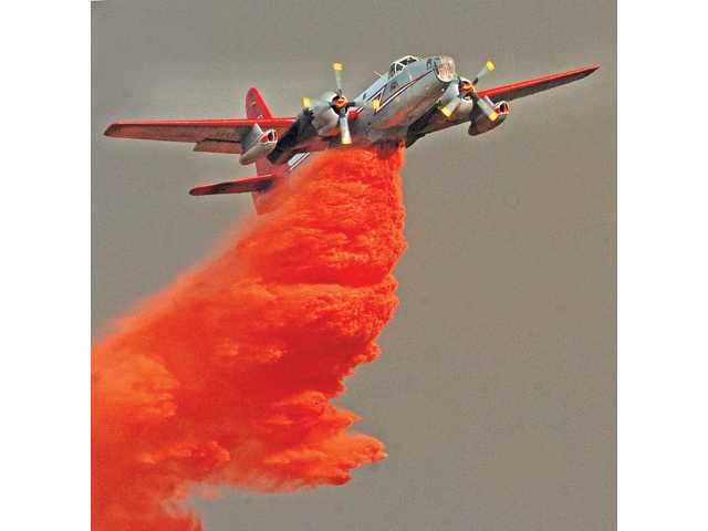 A fixed wing aircraft makes a drop of fire retardant near a home in Acton on Aug. 30, 2009 during the Station Fire. Dan Watson/The Signal